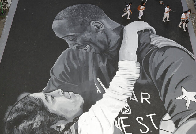 Students walk beside a giant mural of former NBA basketball player Kobe Bryant and daughter Gianna at a basketball court in Taguig, south of Manila, Philippines on Tuesday, Jan. 28, 2020. Artists in this tenement building gathered and painted this image after learning of Bryant's death. Bryant, his daughter and 7 others died in a helicopter crash. (AP Photo/Aaron Favila)