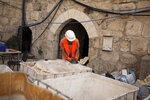 A worker prepares material to restore stone work inside the Tower of David Museum in the Old City of Jerusalem, Wednesday, Oct. 28, 2020. Jerusalem's ancient citadel is devoid of tourists due to the pandemic and undergoing a massive restoration and conservation project. (AP Photo/Maya Alleruzzo)
