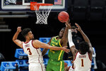 Oregon forward Eugene Omoruyi, center, fights for a rebound with Southern California forward Isaiah Mobley (3) and forward Chevez Goodwin (1) during the first half of a Sweet 16 game in the NCAA men's college basketball tournament at Bankers Life Fieldhouse, Sunday, March 28, 2021, in Indianapolis. (AP Photo/Jeff Roberson)