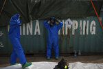 FILE - In this August 10, 2020 file photo, French emergency workers, part of a special unit working with chemicals, suit up near the site of last week's explosion, in the port of Beirut, Lebanon.  For many Lebanese, their greatest hope for credible answers about the blast that wrecked much of their capital lies with outsiders.  (AP Photo/Felipe Dana, File)