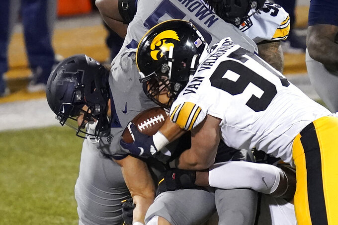Iowa defensive lineman Zach VanValkenburg (97) tackles Illinois running back Chase Brown during the second half of an NCAA college football game Saturday, Dec. 5, 2020, in Champaign, Ill.  (AP Photo/Charles Rex Arbogast)