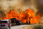 Flames flare behind firefighters and fire trucks at the Apple Fire in Cherry Valley, Calif., Saturday, Aug. 1, 2020. A wildfire northwest of Palm Springs flared up Saturday afternoon, prompting authorities to issue new evacuation orders as firefighters fought the blaze in triple-degree heat.(AP Photo/Ringo H.W. Chiu)