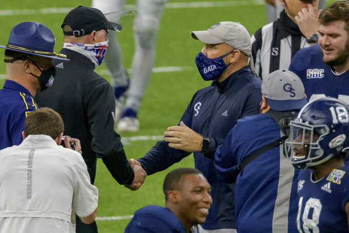 Louisiana Tech coach Skip Holtz, left, congratulates Georgia Southern coach Chad Lunsford after Georgia Southern's win in the New Orleans Bowl NCAA college football game in New Orleans, Wednesday, Dec. 23, 2020. (AP Photo/Matthew Hinton)