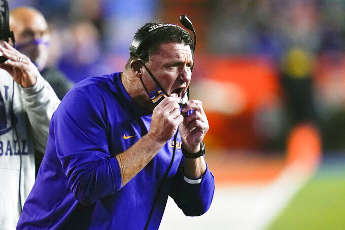 LSU coach Ed Orgeron shouts instructions to players on the field during the first half of the team's NCAA college football game against Florida, Saturday, Dec. 12, 2020, in Gainesville, Fla. (AP Photo/John Raoux)