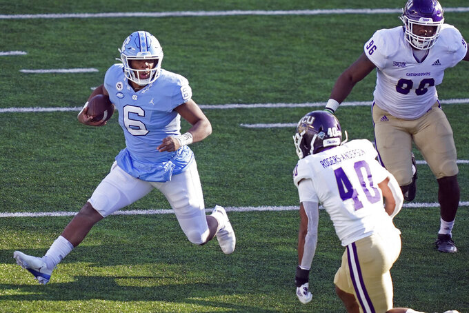 North Carolina quarterback Jacolby Criswell (6) runs while Western Carolina safety La Rogers-Anderson (40) looks to tackle during the second half of an NCAA college football game in Chapel Hill, N.C., Saturday, Dec. 5, 2020. (AP Photo/Gerry Broome)
