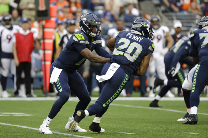 Seattle Seahawks quarterback Geno Smith, left, hands off to running back Rashaad Penny (20) during the first half of the team's NFL football preseason game against the Denver Broncos, Thursday, Aug. 8, 2019, in Seattle. (AP Photo/Elaine Thompson)