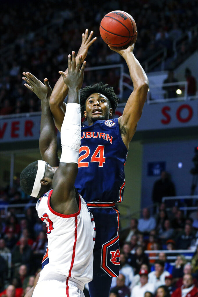 Auburn forward Anfernee McLemore (24) puts up a shot over South Alabama forward Josh Ajayi (33) during the second half of an NCAA college basketball game, Tuesday, Nov. 12, 2019, in Mobile, Ala. Auburn won 70-69. (AP Photo/Butch Dill)