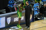 Oregon head coach Dana Altman talks with forward Eugene Omoruyi, left, at the end of a Sweet 16 game against Southern California in the NCAA men's college basketball tournament at Bankers Life Fieldhouse, Sunday, March 28, 2021, in Indianapolis. Southern California won 82-68. (AP Photo/Darron Cummings)