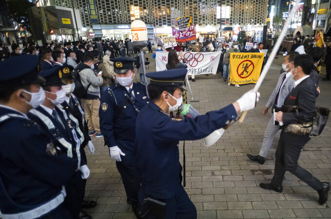 FILE - In this March 25, 2021, file photo, police officers start moving to secure streets as protesters and their supporters, background, start their march against the going ahead of the Olympic and Paralympic Games (Tokyo 2020) in Tokyo. (AP Photo/Hiro Komae, File)