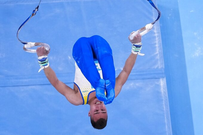 Milad Karimi, of Kazakhstan, performs on the rings during men's artistic gymnastic qualifications at the 2020 Summer Olympics, Saturday, July 24, 2021, in Tokyo. (AP Photo/Morry Gash)