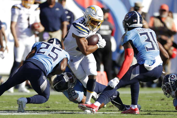 Los Angeles Chargers running back Austin Ekeler (30) carries the ball against Tennessee Titans defenders Adoree' Jackson (25) and Kevin Byard (31) in the first half of an NFL football game Sunday, Oct. 20, 2019, in Nashville, Tenn. (AP Photo/James Kenney)