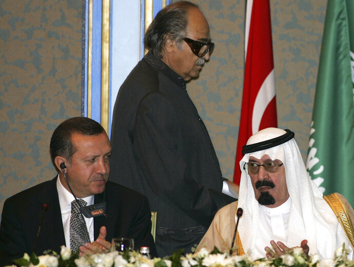 FILE - In this Aug. 10, 2006 file photo, Turkish Prime Minister Recep Tayyip Erdogan, left, and King Abdullah of Saudi Arabia, right, applaud after Islamic Chamber of Commerce and Industry President Sheikh Saleh Abdullah Kamel, center, made a speech during a meeting at the Ottoman era Ciragan Palace in Istanbul, Turkey. Billionaire Saudi businessman Saleh Abdullah Kamel, who founded the banking and real estate conglomerate Dallah Albaraka Group, has died at the age of 79. His business empire grew in the late 1960′s, at the same time that the kingdom was using its oil wealth to rapidly develop and in need of homegrown companies to build roads, highways and cities. (AP Photo/Murad Sezer, File)