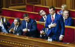 A newly elected Ukraine's prime minister Oleksiy Honcharuk, right, reacts after his nominated during parliament session in Kyiv, Ukraine, Thursday, Aug. 29, 2019. Parliament in Ukraine has opened for its first session since an election last month. (AP Photo/Efrem Lukatsky)