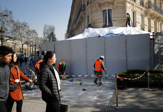 Tourists watch workers as they set up steel protections on the famed restaurant Fouquet's in Paris, Friday, March 22, 2019. French President Emmanuel Macron has announced that soldiers will be deployed across the country to help maintain security during yellow vest protests planned this weekend. (AP Photo/Christophe Ena)