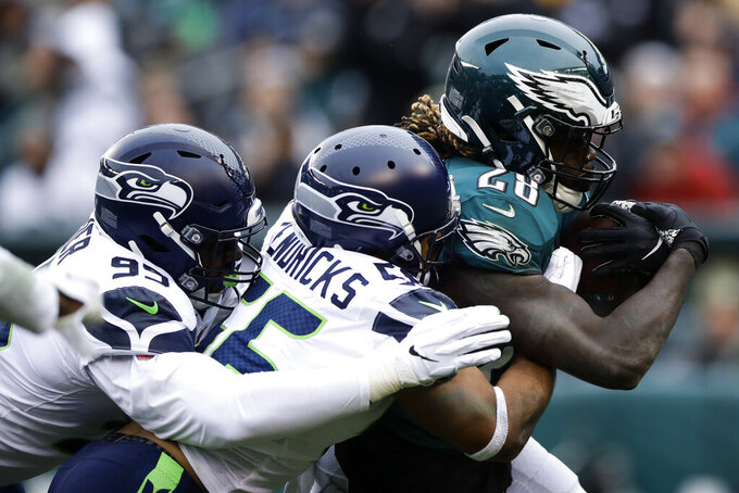 Philadelphia Eagles' Jay Ajayi (28) is tackled by Seattle Seahawks' Mychal Kendricks (56) and L.J. Collier (95) during the first half of an NFL football game, Sunday, Nov. 24, 2019, in Philadelphia. (AP Photo/Matt Rourke)