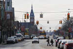 In this Tuesday, Jan. 7, 2020 photo, pedestrians cross S. Monroe St. in Monroe, Mich. Monroe County, population 150,000, has suffered six military casualties since 2001, putting it above the national per capita averages.  (AP Photo/Carlos Osorio)
