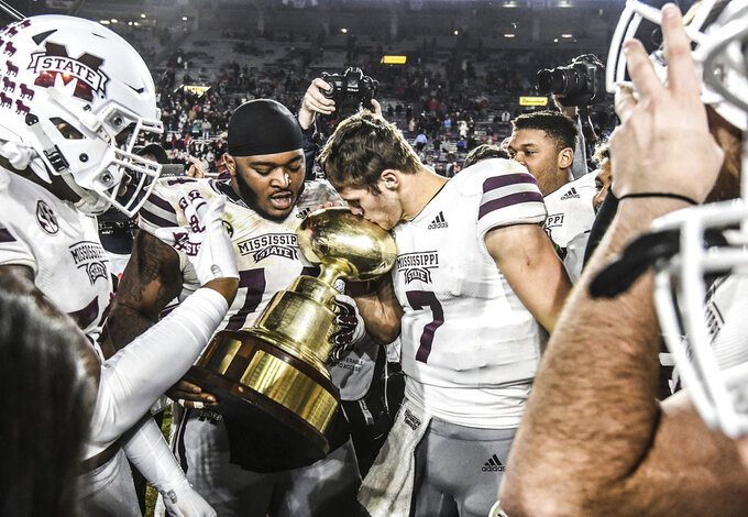 Mississippi State offensive lineman Elgton Jenkins (74) and quarterback Nick Fitzgerald (7) kiss the Golden Egg following a win over Mississippi in Oxford, Miss., Thursday, Nov. 22, 2018. (Bruce Newman, Oxford Eagle via AP)