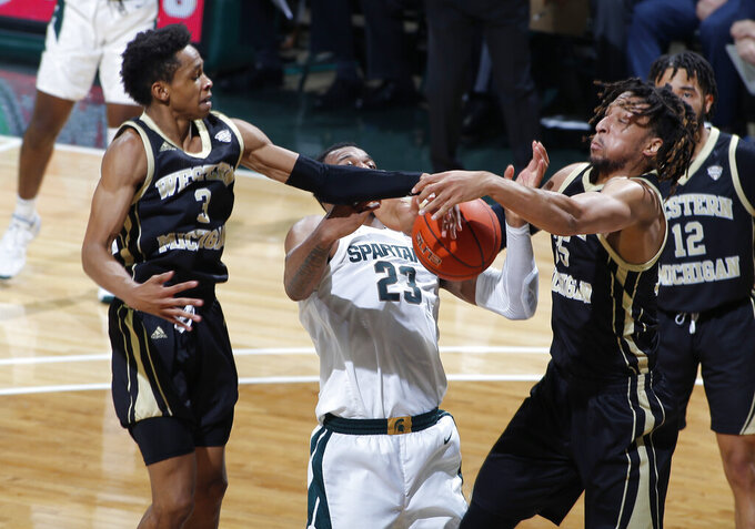 Western Michigan's B Artis White, left, and Brandon Johnson, right, and Michigan State's Xavier Tillman fight for a rebound during the first half of an NCAA college basketball game, Sunday, Dec. 29, 2019, in East Lansing, Mich. (AP Photo/Al Goldis)