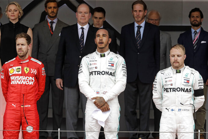 Winner Mercedes driver Lewis Hamilton of Britain, center, 2nd placed Ferrari driver Sebastian Vettel of Germany, left, and 3rd placed Mercedes driver Valtteri Bottas of Finland, right, stand on the podium after the Monaco Formula One Grand Prix race, at the Monaco racetrack, in Monaco, Sunday, May 26, 2019. Charlene, Princess of Monaco in the background on the left, Prince Albert II of Monaco behind Hamilton. (AP Photo/Luca Bruno)