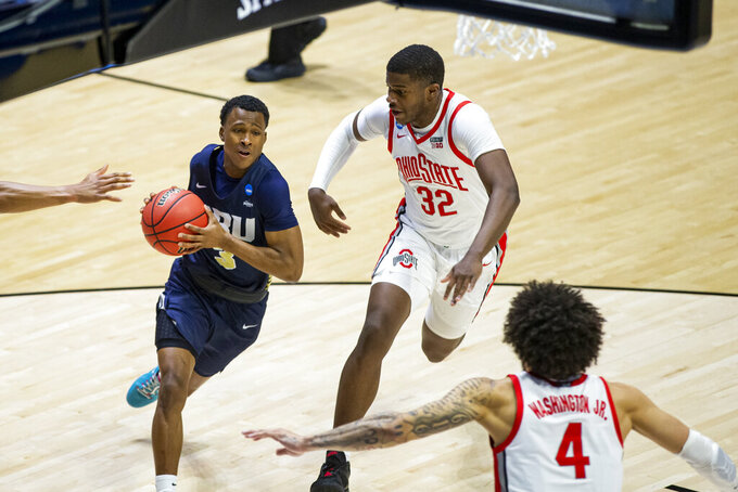 Oral Roberts' Max Abmas (3) drives against Ohio State's E.J. Liddell (32) and Duane Washington Jr. (4) during the first half of a First Round game in the NCAA men's college basketball tournament, Friday, March 19, 2021, at Mackey Arena in West Lafayette, Ind. (AP Photo/Robert Franklin)