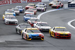 Kyle Busch (18) and Joey Logano (22) lead the pack out of Turn 2 in a NASCAR Cup Series auto race at Charlotte Motor Speedway in Concord, N.C., Sunday, Oct. 11, 2020. (AP Photo/Nell Redmond)