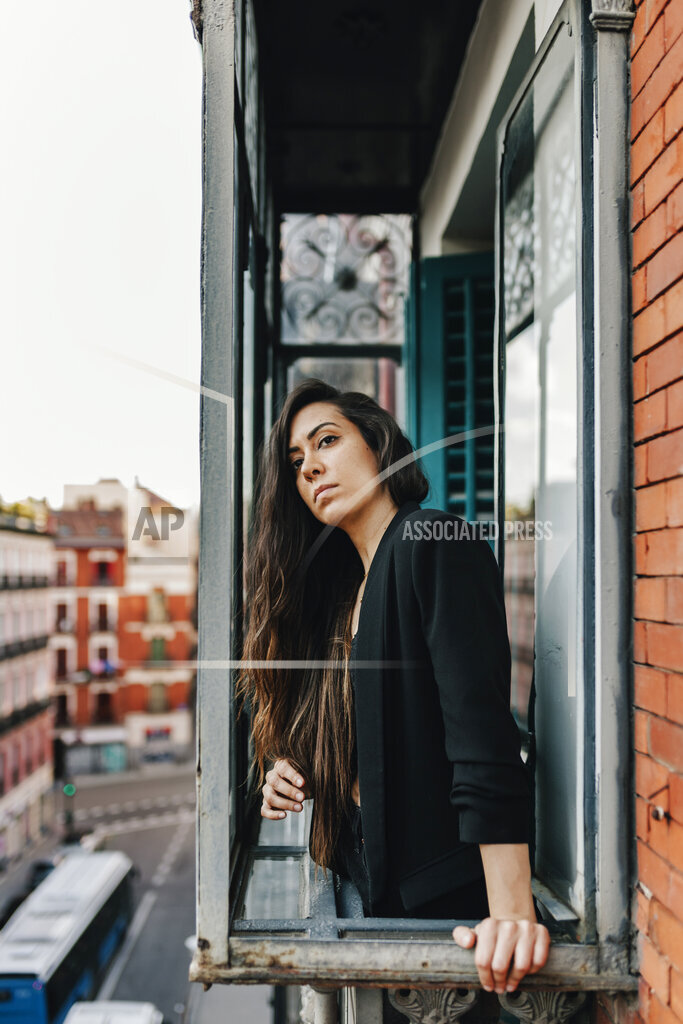 Lonely woman standing at window