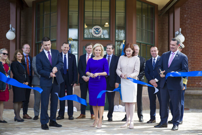 Outgoing Homeland Security Secretary Kirstjen Nielsen, front center left, cuts a ribbon accompanied by outgoing acting deputy secretary Claire Grady, front center right, Incoming Acting Homeland Security Secretary Kevin McAleenan, front left, and Administrator of the Transportation Security Administration David Pekoske, front right at the dedication ceremony at the Homeland Security headquarters Center Building at the old St. Elizabeths Hospital, Wednesday, April 10, 2019, in Washington. (AP Photo/Alex Brandon)