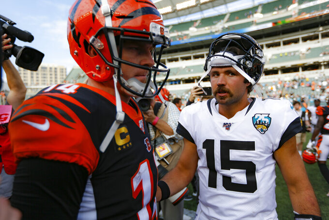 Jacksonville Jaguars quarterback Gardner Minshew (15) meets with Cincinnati Bengals quarterback Andy Dalton (14) after an NFL football game, Sunday, Oct. 20, 2019, in Cincinnati. (AP Photo/Frank Victores)