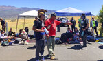 In this July 15, 2019, photo from video, protest leader Kaho'okahi Kanuha, center left, talks to demonstrators, some of whom have chained themselves to a cattle guard on a road at the base of Mauna Kea on Hawaii's Big Island. For activists who say they're protecting Mauna Kea, the fight against the proposed Thirty Meter Telescope is a boiling point in Hawaiian history: the overthrow on the Hawaiian kingdom, battles over land, water and development and questions about how the islands should be governed. (AP Photo/Caleb Jones)