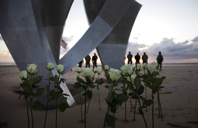 Men in a vintage US WWII uniforms stand behind flowers left at Les Braves monument after a D-Day 76th anniversary ceremony in Saint Laurent sur Mer, Normandy, France, Saturday, June 6, 2020. Due to coronavirus measures many ceremonies and memorials have been cancelled in the region with the exception of very small gatherings. (AP Photo/Virginia Mayo)