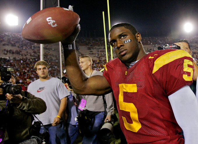 "FILE - In this Nov. 19, 2005, file photo, Southern California tail back Reggie Bush walks off the field holding the game ball after the Trojans defeated Fresno State, 50-42, at the Los Angeles Coliseum. The former star running back had been prohibited from interacting in an official capacity with the school he played for from 2003-05 since NCAA sanctions handed down in 2010. Bush and USC were penalized for him and his family receiving impermissible benefits while he was still in school. USC President Carol Folt wrote in a letter to Bush on Wednesday, June 10, 2020, that he could now ""be afforded the privileges and courtesies extended to all Trojan football alums.""(AP Photo/Kevork Djansezian, File)"
