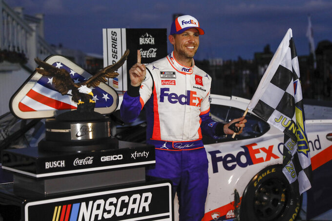 FILE - In this June 28, 2020, file photo, Denny Hamlin celebrates after winning the NASCAR Cup Series auto race at Pocono Raceway, in Long Pond, Pa. Denny Hamlin and Kevin Harvick flipped their 1-2 finish in Pocono's doubleheader weekend last year but they each come back for this weekend's races winless and trying to chase Kyle Larson. (AP Photo/Matt Slocum, File)