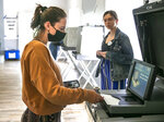 Sydney Johnson inserts her casts her ballot as election official Clare Lewis watches near Stafford, Va., Tuesday, June 8, 2021. It was Johnson's first time voting. (Peter Cihelka/The Free Lance-Star via AP)