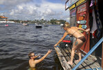 Colette Murray takes a swim up order at Jay's Sand Bar Floating BBQ, serving pork nachos and alligator bites to hungry boaters and bikini-wearing partiers on the sandbar in Ft. Lauderdale,  Fla., on Saturday, Oct. 10, 2020. (Mike Stocker/South Florida Sun-Sentinel via AP)