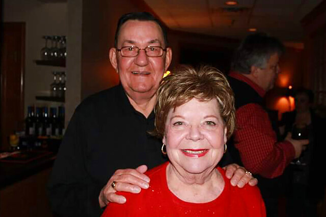 In this 2011 family photo provided by Dawn Bouska, Charles Recka and his wife, Patricia Recka, pose for a photo at a banquet in Naperville, Ill. Charles Recka died on March 12, 2020. Deep into the obituary for 87-year-old Recka is the short announcement that