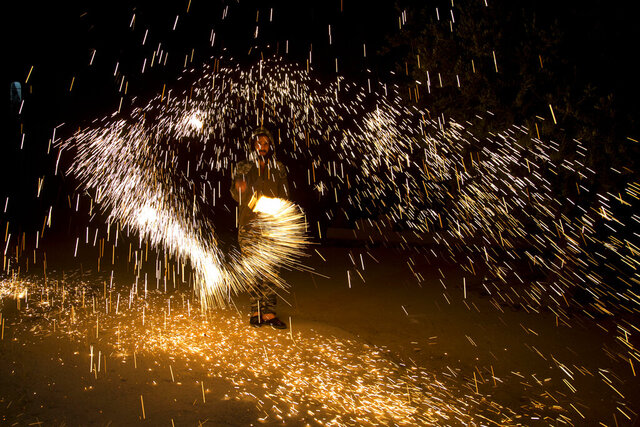 A Palestinian plays with fireworks as he celebrates the start of the Muslim holy month of Ramadan in the West Bank city of Nablus, Thursday, April. 23, 2020.