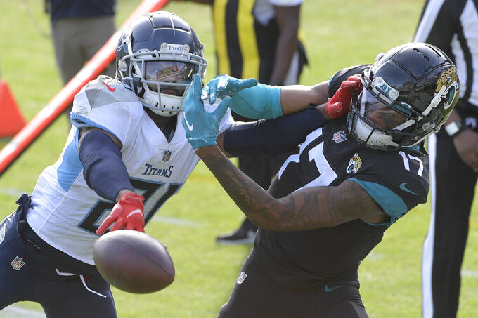 Tennessee Titans cornerback Malcolm Butler, left, breaks up a pass intended for Jacksonville Jaguars wide receiver DJ Chark Jr. (17) during the second half of an NFL football game, Sunday, Dec. 13, 2020, in Jacksonville, Fla. (AP Photo/Phelan M. Ebenhack)