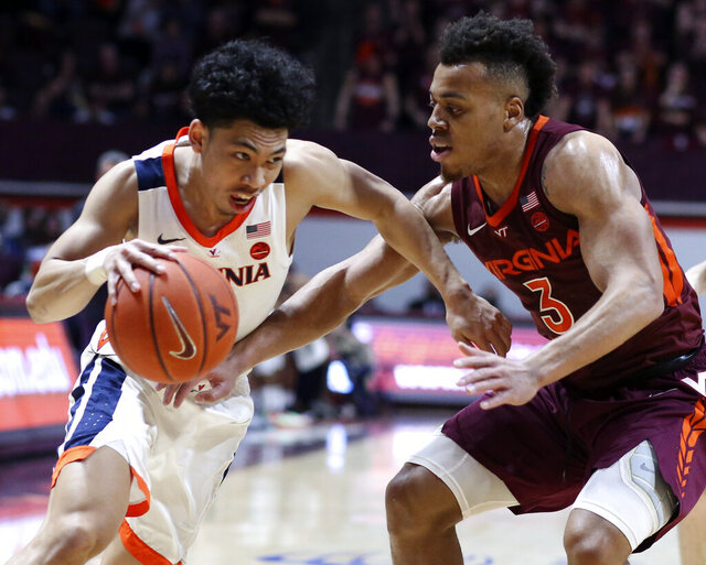 Virginia's Kihei Clark drives on Virginia Tech's Wabissa Bede (3) during the first half of an NCAA college basketball game Wednesday, Feb. 26, 2020, in Blacksburg, Va. (Matt Gentry/The Roanoke Times via AP)