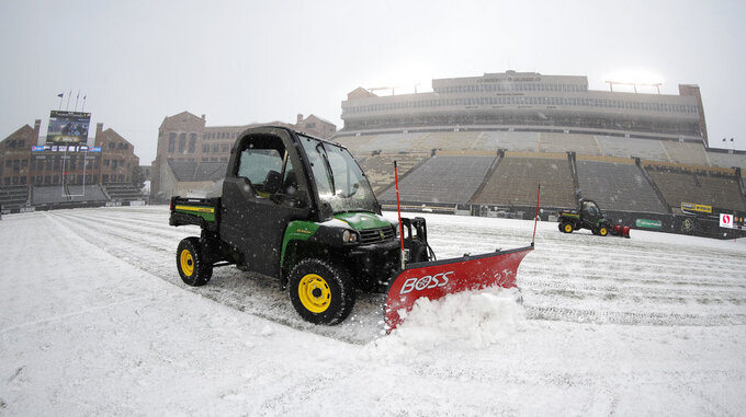 Grounds crew workers clear snow from the playing surface of Folsom Field before the first half of an NCAA college football game between Utah and Colorado Saturday, Nov. 17, 2018, in Boulder, Colo. A fall storm packing cold temperatures and light snow has swept over the intermountain West. (AP Photo/David Zalubowski)