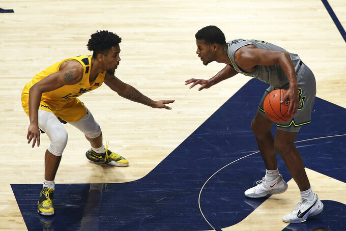 Baylor guard Jared Butler (12) is defended by West Virginia guard Taz Sherman during the second half of an NCAA college basketball game Tuesday, March 2, 2021, in Morgantown, W.Va. (AP Photo/Kathleen Batten)