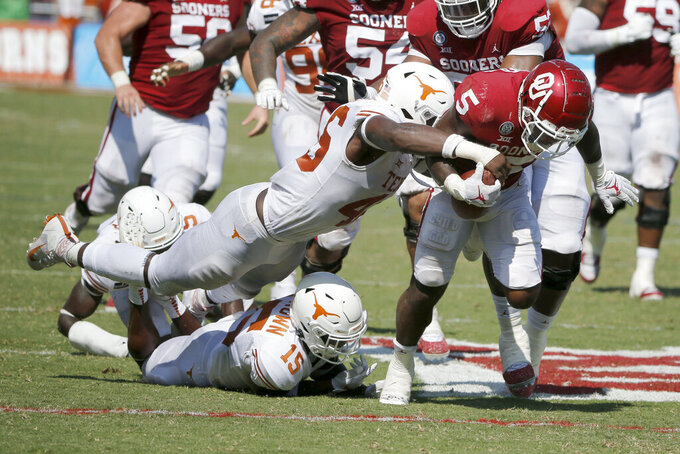 Texas linebacker Joseph Ossai (46) forces a fumble by Oklahoma running back T.J. Pledger (5) during an NCAA college football game in Dallas, Saturday, Oct. 10, 2020. (AP Photo/Michael Ainsworth)