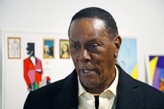 FILE - In this Jan. 17, 2019 file photo, Richard Phillips stands next to some of his artwork during an interview at the Community Art Gallery in Ferndale, Mich. Phillips was exonerated of murder in 2018 after 45 years in prison. The state of Michigan has agreed to pay $1.5 million to Phillips. The attorney general's office said Friday, May 17, 2019, it has settled a lawsuit filed Phillips. He made a claim under a Michigan law that compensates the wrongly convicted. (AP Photo/Carlos Osorio File)