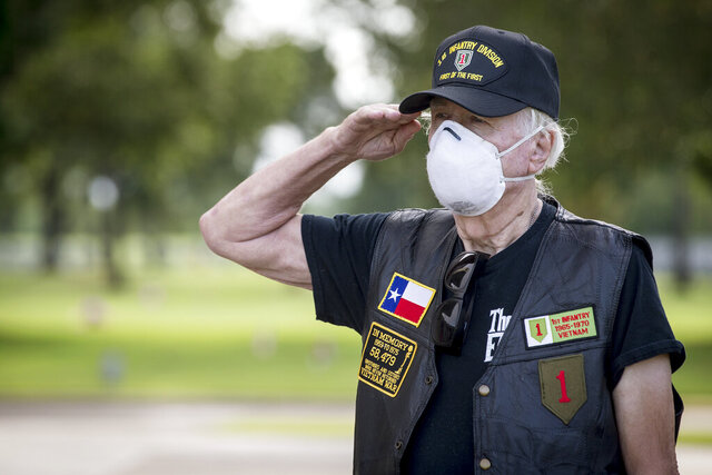Ron Brewton salutes as taps is played during a scaled down Memorial Day ceremony at Houston National Cemetery, Monday, May 25, 2020, in Houston. Due to coronavirus restrictions, the usual ceremony limited the number of people attending. (Brett Coomer/Houston Chronicle via AP)