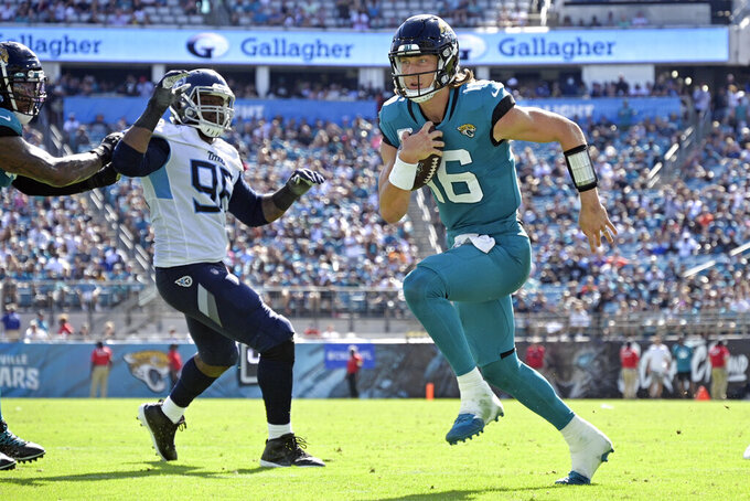 Jacksonville Jaguars quarterback Trevor Lawrence (16) runs for a touchdown past Tennessee Titans defensive end Denico Autry, left, during the second half of an NFL football game, Sunday, Oct. 10, 2021, in Jacksonville, Fla. (AP Photo/Phelan M. Ebenhack)