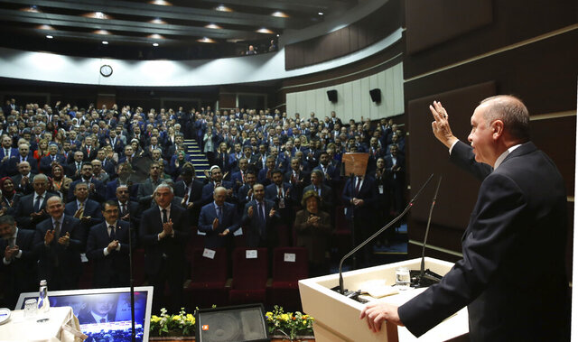 Turkey's President Recep Tayyip Erdogan gestures as he addresses the members of his ruling party, in Ankara, Turkey, Thursday, Dec. 26, 2019. Erdogan says Thursday his government will submit a bill to parliament that would allow Turkey to send troops to Libya, in support of the U.N.-backed government there. Erdogan said the Libyan government, which controls the capital, Tripoli, has