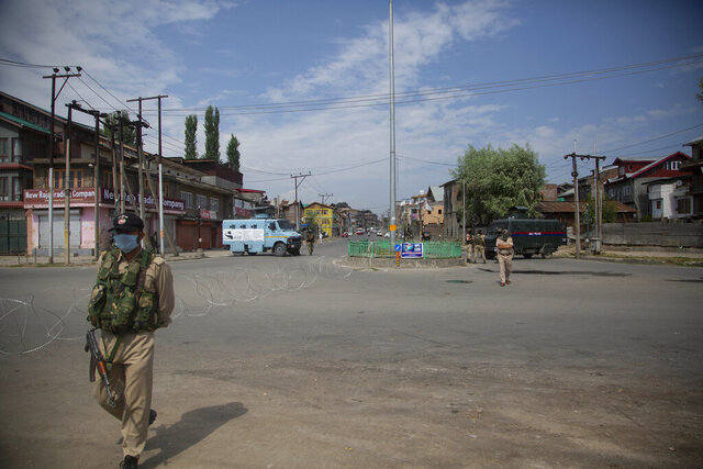 "Policemen and paramilitary soldiers patrol a road during curfew in Srinagar, Indian controlled Kashmir, Tuesday, Aug. 4, 2020. Authorities clamped a curfew in many parts of Indian-controlled Kashmir on Tuesday, a day ahead of the first anniversary of India's controversial decision to revoke the disputed region's semi-autonomy. Shahid Iqbal Choudhary, a civil administrator, said the security lockdown was clamped in the region's main city of Srinagar in view of information about protests planned by anti-India groups to mark Aug. 5 as ""black day."