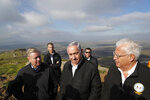 FILE - In this March 11, 2019, file photo, Israeli Prime Minister Benjamin Netanyahu, center, Republican U.S. Senator Lindsey Graham, left, and U.S. Ambassador to Israel David Friedman, right, visit the border between Israel and Syria in the Israeli-held Golan Heights. Graham says he will push for American recognition of Israeli sovereignty over the Golan Heights, a territory Israel captured from Syria in the 1967 Mideast War. (Ronen Zvulun/Pool Photo via AP, File)