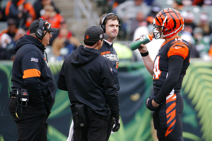 Cincinnati Bengals quarterback Andy Dalton (14) speaks with head coach Zac Taylor, center right, during the second half of an NFL football game against the New York Jets, Sunday, Dec. 1, 2019, in Cincinnati. (AP Photo/Frank Victores)