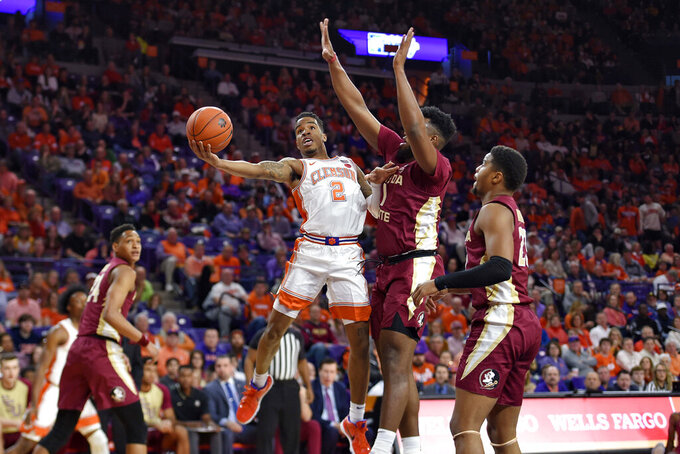 Clemson's Al-Amir Dawes (2) shoots while defended by Florida State's RaiQuan Gray during the first half of an NCAA college basketball game Saturday, Feb. 29, 2020, in Clemson, S.C. (AP Photo/Richard Shiro)