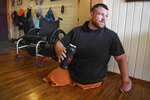 In this Aug. 7, 2019 photo, Thomas (Tomy) Parker, a 29-year-old Marine Corp veteran and triple amputee, prepares his pre-workout drink before a wheelchair run in his home in Ronan, Mont. The Montana Marine who lost his legs to an IED in Afghanistan came home to a hero's welcome and a house was built for him, but he lost it to addiction. Parker attended rehab, is being treated for PTSD and is now competing in wheelchair races. Parker often wears the same orange pants he was issued while serving time for possession of methamphetamine and heroin. (Tommy Martino/The Missoulian via AP)